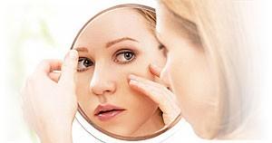 Charis Beauty Clinic, Islington. Model looking into mirror.